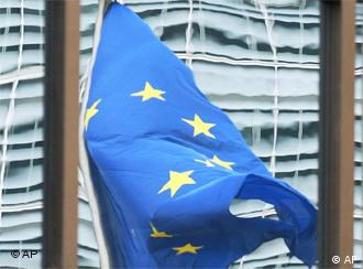 The EU flag is mirrored in the glasswork of the EU Council headquarters in Brussels