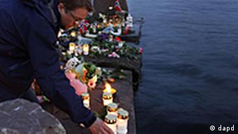 A man lights a candle close to the Utoya island in Utvica near Sundvollen near Oslo, Norway, Tuesday, July 26, 2011, in memory of the eight people killed in Friday's blast in Oslo and the 68 who died in the shooting at the youth camp on Utoya. (Foto:Ferdinand Ostrop/AP/dapd)