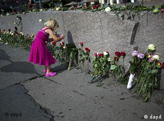 A young girl takes photos at a wall with flowers in memory of the victims of Friday's bomb attack and shooting rampage in Oslo, Norway, Tuesday, July 26, 2011. The defense lawyer for Anders Behring Breivik said Tuesday his client's case suggests he is insane, adding that someone has to take the job of defending him but that he will not take instructions from his client. Geir Lippestad told reporters that the suspect in the bombing on the capital and the brutal attack on a youth camp that killed at least 76 people is not aware of the death toll or of the public's response to the massacre that has rocked the country. (Foto:Emilio Morenatti/AP/dapd)