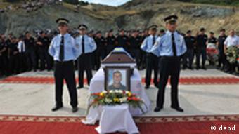 Members of Kosovo Police stand guard next to the coffin of the slain officer Enver Zymberi in the village of Dubovc on Wednesday, July 27, 2011. Zymberi was killed in an ambush during a police operation to take control of two border crossings with Serbia in Kosovo's Serb-dominated north. (Foto:Visar Kryeziu/AP/dapd)