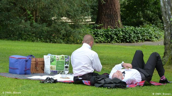 Two men sit on the grass at the Bayreuth Festival