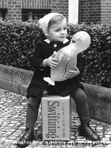 Black-and-white photo of a girl sitting on a CARE package holding a large toy duck