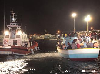 Italian coast guard boat (left) escorts a boat with north African migrants upon arrival on the island of Lampedusa last month