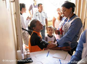 A health worker cares for children at an ICRC mobile clinic