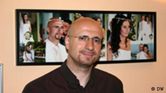 Ilias Courtidis in front of a photo collage portraying him and his wife