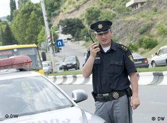 Грузинский полицейский радом с патрульной машиной