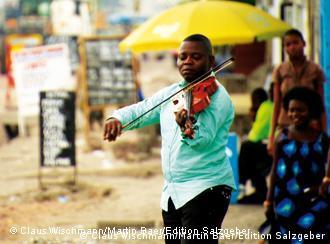 Ein Musiker des 'Orchestre Symphonique Kimbanguiste' spielt auf der Straße (Foto: Edition Salzgeber
