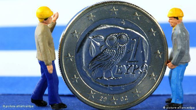 Men lifting a one-euro Greek coin