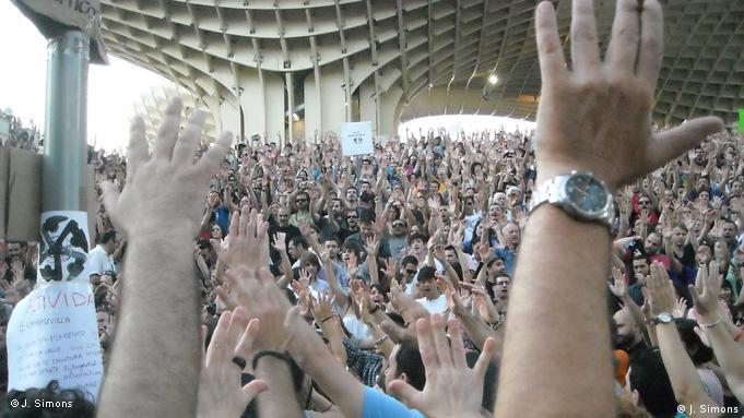 Demonstranten auf dem Plaza Mayor in Sevilla strecken die Hände in die Luft (Foto: Johannes von Simons)