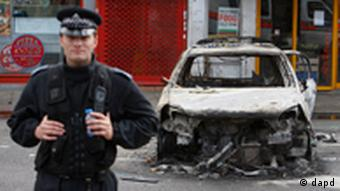 A police officer stands guard in front of a burned police car in Tottenham, north London, Sunday, Aug. 7, 2011 after a demonstration against the death of a local man turned violent and cars and shops were set ablaze. One police officer was hospitalized and seven others were injured during riots after a north London suburb exploded in anger Saturday night following a gathering to protest the Thursday shooting by police of the 29-year-old. (Foto:Akira Suemori/AP/dapd)