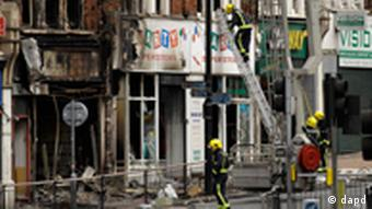 Fire fighters tend to a fire-damaged shop