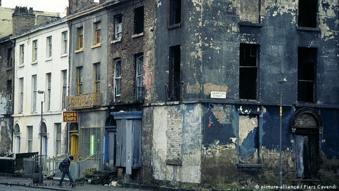 A man walks past a group of derelict buildings in Liverpool, England. Armut; Auswirkung; Britisch; Bürgersteig; Elendsviertel; England; Englisch; Europa; Europäisch; Farbe; F