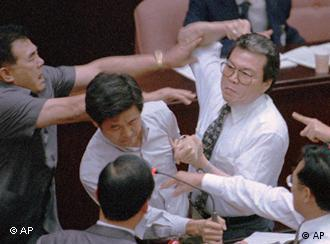 Lin Ming-yi, right, of the ruling Nationalist Party, punches rival lawmaker Huang Chao-hui, second from left, of the opposition Democratic Progressive Party, as Huang made speeches mocking Nationalist Party lawmakers at the Legislature podium Tuesday, July 18, 1995. (AP Photo/CNA)