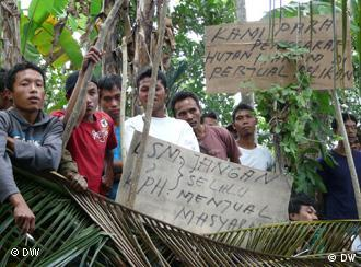 Villagers protest with signs against the international visitors