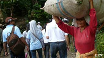A woman balances a bag on her head