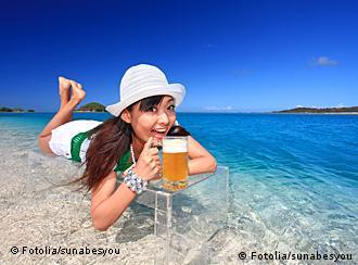 Young woman drinks beer on a beach