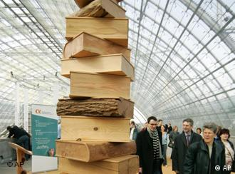A wooden sculpture of stacked books attracts visitors' stares
