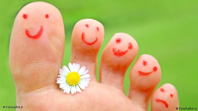 Fuß mit Gänseblümchen und Smily glückliche Füße