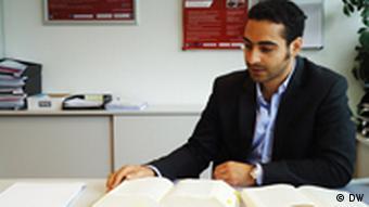 Einer der Absolventen des Masterstudiengangs Deutsches und Türkisches Wirtschaftsrecht, Baran Kizil, blättert am Schreibtisch sitzend in einem Buch, Foto von Anja Fähnle DW