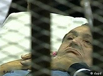 In this video image taken from Egyptian State Television 83-year-old former Egyptian president Hosni Mubarak gestures as he lies on a bed within a cage at the court building in Cairo Monday Aug. 15, 2011. Mubarak has returned to a Cairo court on a stretcher for the next session of his trial on charges of corruption and complicity in killing protesters during Egypt's uprising. (Foto:Egyptian State TV/AP/dapd) EGYPT OUT