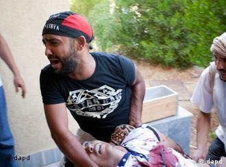 A Libyan rebel evacuates a wounded man after a shelling attack in Zawiya