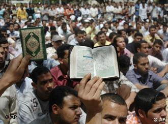 Muslim Brotherhood students hold a copy of the Quran during a protest at the al-Azhar university in Cairo, Egypt, Wednesday, April 16, 2008. Thousands of Muslim Brotherhood students in two Egyptian universities demonstrated Wednesday against the jailing of 25 members of the group for membership of an outlawed organization and anti-government activities. (AP Photo/Hossam Ali)
