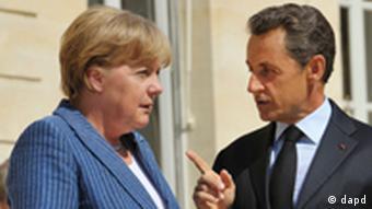 France's President Nicolas Sarkozy, right, speaks to German Chancellor Angela Merkel