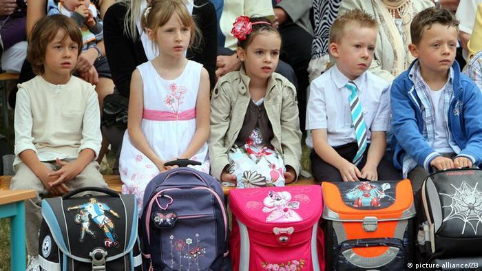 Mädchen und Jungen sitzen mit ihren Schulranzen während der Einschulungsfeier in der Grundschule Plötzky (Salzlandkreis) und beobachten eine Vorführung älterer Schüler (Foto: dpa)