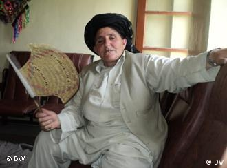 Bibi Hakmeena sitting on a sofa dressed in white men's clothing and black turban