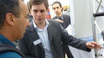 Informationsstand auf der Intersolar von der Firma Autarcon, Geschäftsführer Florian Benz erklärt. Die Firma entwickelte ein autarke Trinkwasseranlage die mit einem Solarmodul betrieben wird. Sie eignet sich gut für Entwicklungs- und Schwellenländer. Sie ist sehr einfach und innovativ und desinfiziert das Wasser mit einer eigenen Chlorproduktion; München Juni 2011; Foto: DW Gero Rueter