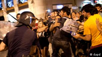 Riot police officers clash with demonstrators during a protest against the visit of Pope Benedict XVI in Madrid