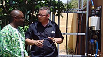 Geschäftsführer Alexander Goldmaier erklärt die Funktionsweise Snsumana Sillah. Sillah ist Repräsentant des Gesundheitsministeriums von der westafrikanischen Republik the Gambia. Die Firma Autarcon wurde für ihr wartungsarmes einfaches Wasseraufbereitungssystem u.a. mit dem Intersolarpreis 2011 ausgezeichnet. Das System kann ohne Zusatzstoffe und ohne Stromanbindung Flusswasser mittels Elektrolyse entkeimen. Das elektrolytisch erzeugte Chlor schützt zudem dauerhaft vor Verkeimung. Dieses System wurden in Pakistan, Brasilien und Gamiba inzwischen aufgestellt. Copyright: Autarcon