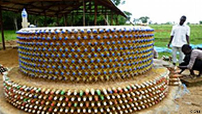 A round house with bottle necks sticking out of the wall