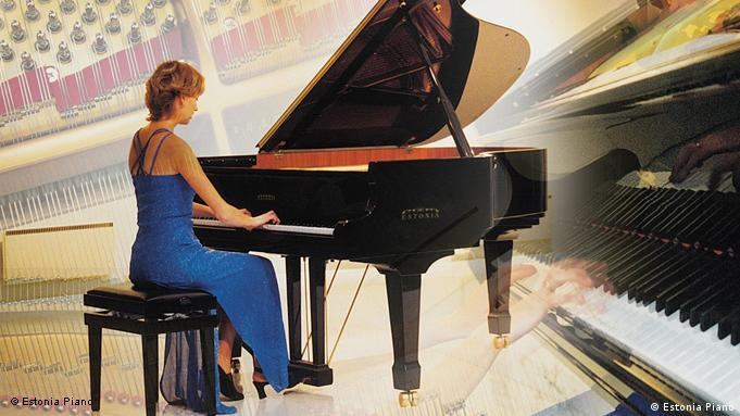 A woman in a blue dress plays an Estonia Piano