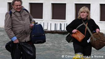 Tourists don waders to escape the flooding in Venice