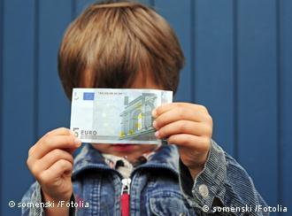 Junge mit Geldschein vor dem Gesicht (Foto: Fotolia)
