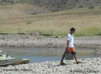 A person carrying two buckets of water from a lake