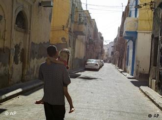 A libyan man with his daughter walks along an empty street in downtown Tripoli, Libya, Tuesday, Aug. 23, 2011. (AP Photo/Sergey Ponomarev)
