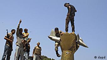 Rebel fighters celebrate as they stand on top of the monument inside Moammar Gadhafi's compound in Bab Al-Aziziya in Tripoli, LIbya, Wednesday, Aug. 24, 2011. The rebels say they have now taken control of nearly all of Tripoli, but sporadic gunfire could still be heard Wednesday, and Gadhafi loyalists fired shells and assault rifles at fighters who had captured the Libyan leader's personal compound one day earlier. (Foto:Sergey Ponomarev/AP/dapd)