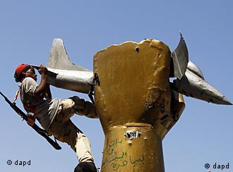 A rebel fighter climbs on top of a statue inside Moammar Gadhafi's compound