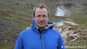 Andri Snær Magnason, isländischer Schriftsteller steht in einer blauen Jacke vor heißen dampfenden Quellen in der Nähe von Reykjavik (Foto: DW / Nadine Wojcik)
