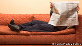 A person sitting on a sofa behind a newspaper Photo: Fotolia/Alistair Cotton # 165887