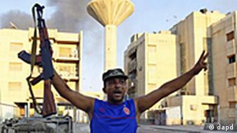 A Libyan rebel raises his arms in the air with an assault rifle in one of his hands