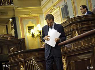 LE Spain's Prime Minister Jose Luis Rodriguez Zapatero leaves the stage after speaking at the Spanish Parliament in Madrid, Tuesday Aug. 23, 2011. Spain's prime minister and the opposition leader agreed to work on amending the Constitution to limit the government deficit. (AP Photo/Daniel Ochoa de Olza)