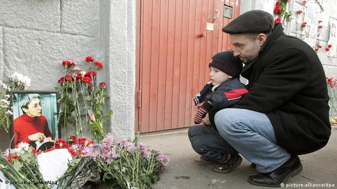 A man and a young boy crouch beside bunches of flowers and a photo of Politkovskaya outside the apartment block where she was killed, on the third anniversary of her murder. (Photo: EPA/MAXIM SHIPENKOV (c) dpa)