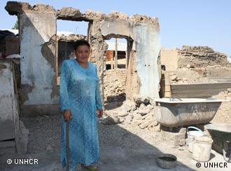 Oftoboy Kadibayeva stands outside her destroyed home in Kyrgyzstan