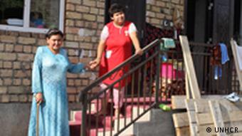Oftoboy Kadibayeva with her daughter on the steps of her home in Kyrgyzstan