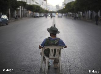A rebel in Libya sits on a small garden chair, surveying a deserted street