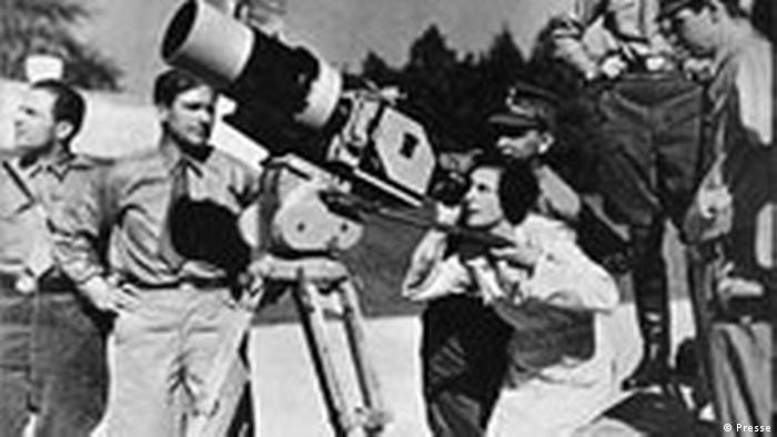 Foto antiga com mulher diante de câmera cercada de homens