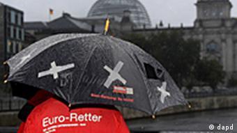 Ein Mitglied des Verbandes Die Jungen Unternehmer (BJU) haelt am Mittwoch (07.09.11) in Berlin nahe der Marschallbruecke in Sichtweite des Reichstagsgebaeudes bei einer Protestaktion gegen den Euro-Rettungsschirm (EFSF) einen Regenschirm mit dem Aufdruck Euro-Rettung: So nicht! www.bju.de und einem Loch. Das Bundesverfassungsgericht verkuendet am Mittwoch sein mit Spannung erwartetes Urteil ueber die Verfassungsmaessigkeit der milliardenschweren Euro-Hilfen Deutschlands. (zu dapd-Text) Foto: Tobias Schaertl/dapd